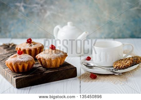 Tasty muffins with raisins and dried cherry on a white wooden table