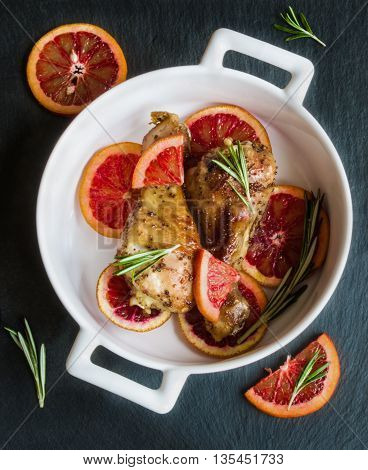 Roasted chicken legs on slices of red oranges in white baking dish. Black slate background. Cooked with the sauce: orange juice mustard olive oil and honey.