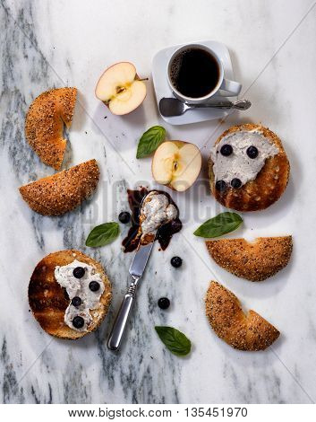 Overhead view of toasted bagels with cream cheese sauce blueberries basil sliced apple and coffee on white marble stone.