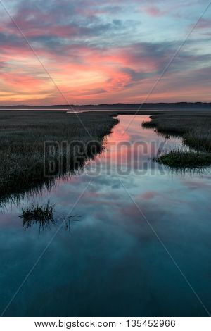 Coastal Wetlands with Dramatic Sunrise and Water Reflections