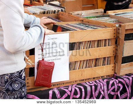 An anonymous woman or girl is searching with hands through wooden crates and cardboard boxes of old music record albums.