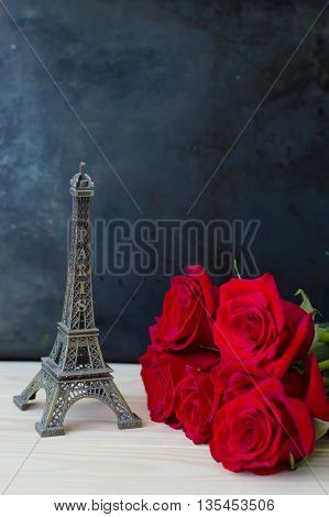 Red roses and small metal miniature of Eiffel Tower on wooden table Love and Romantic concept