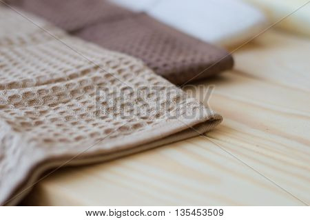 Kitchen towels of brown color on a wooden table selective focus