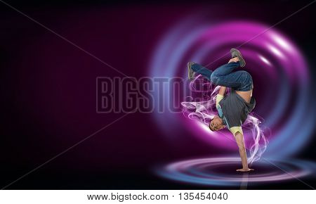 Modern style dancer in jump and lights at background