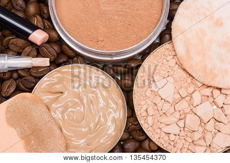 Close-up of concealers, liquid foundation, loose and crushed compact powder on coffee beans. Basic makeup products to create the perfect skin tone and complexion
