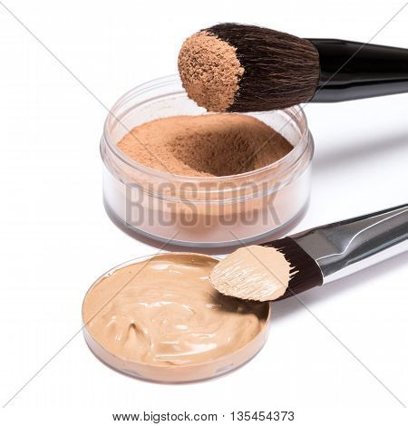 Liquid foundation and open jar of loose cosmetic powder with brushes on white background, side view. Makeup products to even out skin tone and complexion
