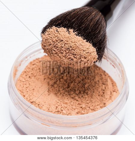 Close-up of makeup brush with loose cosmetic powder on light background. Shallow depth of field, focus on powdery brush tip