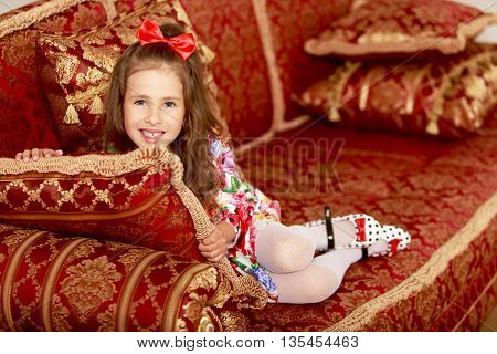 Cute little girl resting on the couch , leaning on a pillow