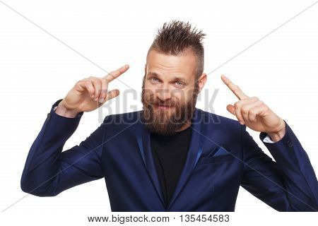 Young bearded man isolated at white background. Close up portrait of guy with beard showing, pointing fingers at his cool hairstyle, looking at camera. Boy style, trendy hipster in blue suit.