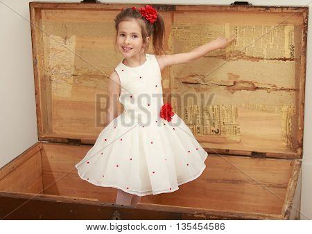 Beautiful little girl in fancy white dress plays in the old grandmother's trunk. Girl shows a finger on an old newspaper which was pasted to the cover.