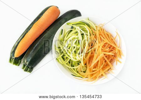 Two zucchini courgettes and carrot with some spiralized in white bowl on white background