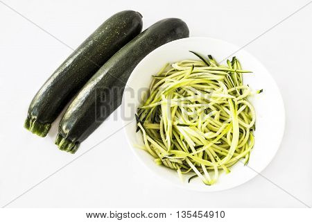 Two zucchini or courgettes with some spiralized in a white bowl on white background
