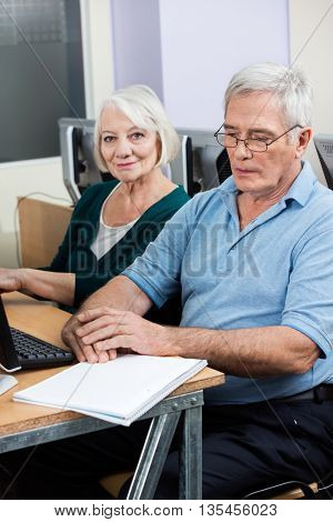 Senior Woman Sitting By Male Classmate During Computer Class