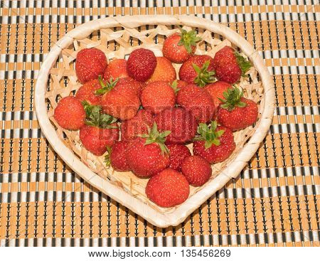 fresh strawberries in a basket heart shape on a wooden table