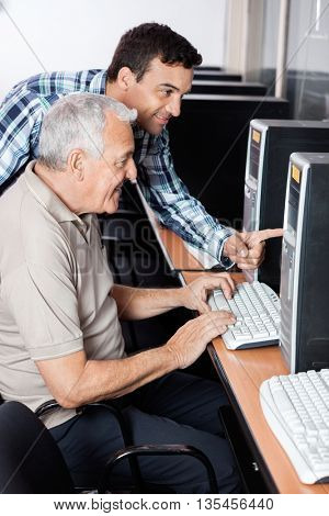 Teacher Assisting Senior Man In Using Computer