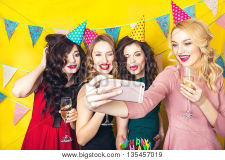 Best friends taking selfie .Portrait of joyful friends toasting and looking at camera at birthday party. Attractive friends celebrating a birthday. Smiling girls with glasses of champagne