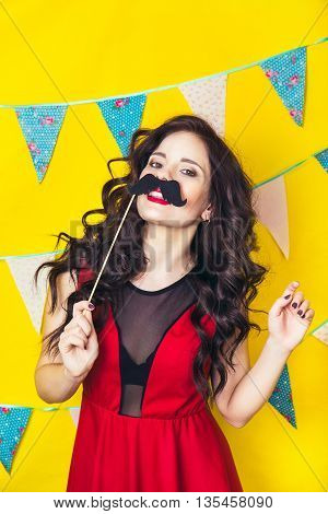 Celebration and party. Having fun. Young pretty woman in red dress and birthday hat is laughing. Colorful studio portrait with yellow background. Girl wearing fake mustaches.