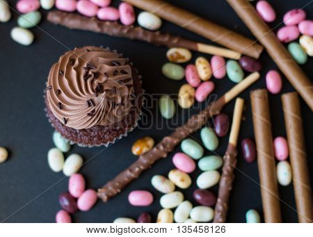 One chocolate cupcake with cream and many sweets and chocolate sticks