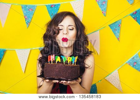 Beautiful caucasian girl blowing candles on her cake. Celebration and party. Having fun. Young pretty woman in red dress and birthday hat is laughing.