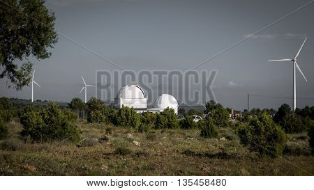 Cloudy day over telescope observatory and windmills