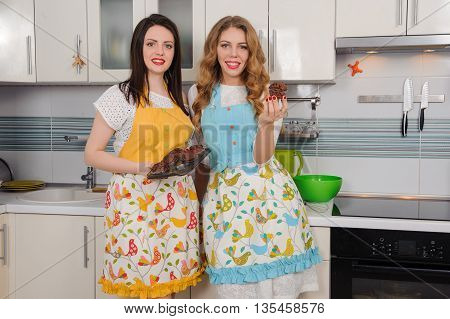 Two happy women housewife in apron at kitchen.