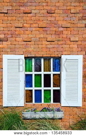 White window and colorful glass on orange brick wall