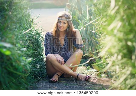 Hippie girl sitting on the ground in the park with green bushes and cactus