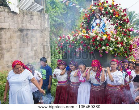 PANCHIMALCO EL SALVADOR - MAY 08 : Salvadoran girls carry an altar with a statue of Virgin Mary during the procession of the Flower & Palm Festival in Panchimalco El Salvador on May 08 2016