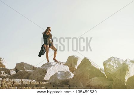 One youg female dressed like a hippie standing at the big rocks
