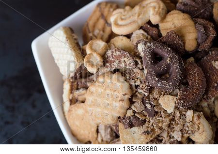 Mix of different sweet cookies in a white plate on black background