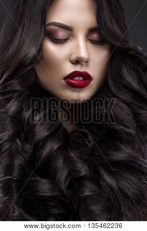 Beautiful brunette model with curls classic makeup and red lips. The beauty of the face. Portrait shot in the studio on a gray background.