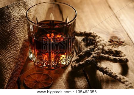 Glass of whiskey and rope on a table