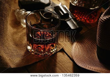 Glass of whiskey, revolver and hat on a table