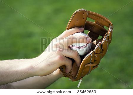 Male hands are holding baseball glove and ball on green background.