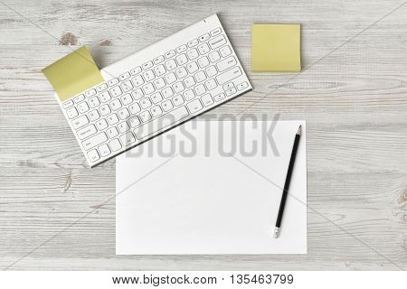 Office workplace with keyboard, pen and white blank paper. Top view composition. Willingness to work overtime. Keeping healthy. Contribution to wellbeing. Workplace of office man.
