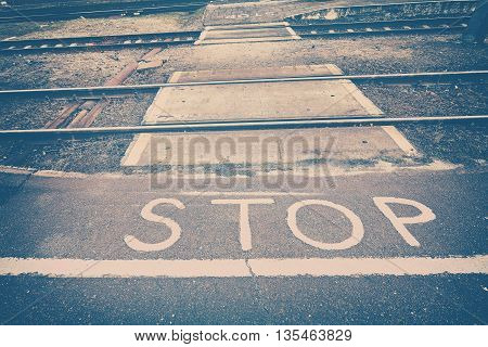 Vintage toned stop sign painted in front of railroad tracks.