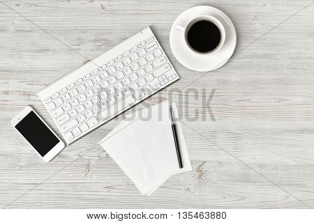 Workplace with cup of coffee, keyboard, smarthphone, white sheets and pen on wooden surface in top view. Workplace of office man or information technology specialist. Office stuff. Readiness for the new. Beginning of something new. First work day. Uplifti