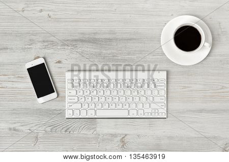 Workplace with cup of coffee, keyboard and smarthphone on wooden surface in top view. Workplace of office man or information technology specialist. Office stuff. Readiness for the new. Beginning of something new. First work day. Uplifting mood. Coffee bre
