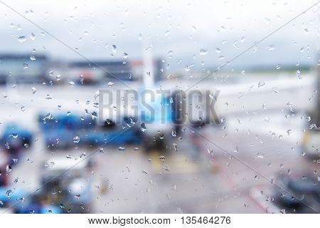 Abstract defocused bokeh of airplane at airport gate with sun coming out after the rain. Modern travel concept and wander lifestyle at sunset. Focus on raindrops with warm vintage filtered look