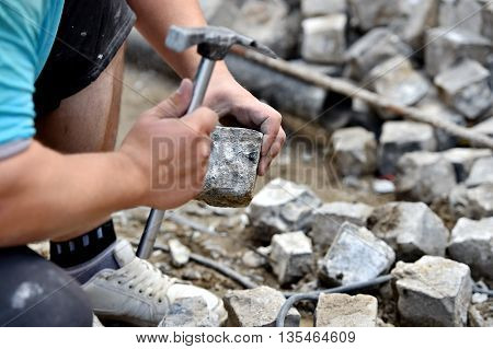 Details with hands of a mason working with cobblestone