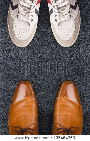 Focus of brown dress shoes against black road