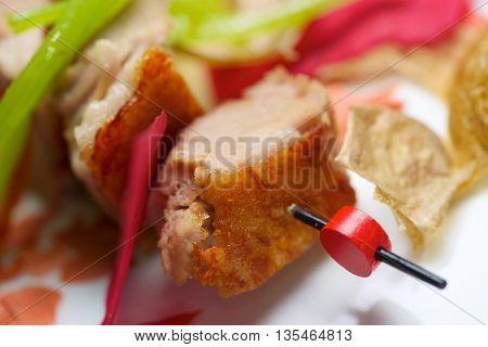 Closeup of a skewer of pork jowls.