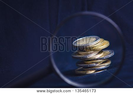Euro money. Coins are isolated on a dark background. Currency of Europe. Balance of money. Building from coins. View through the magnifier