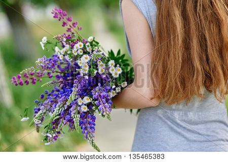 Woman holding a bouquet of blue lupine flowers.