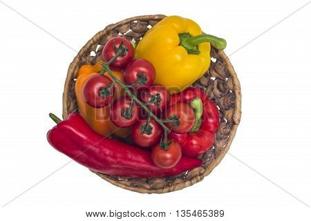 Vegetables: red tomatoes and peppers of different colors lying in a wicker basket on a white isolated background