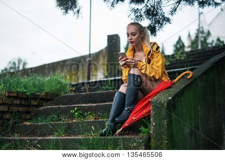 Woman sitting outdoors on a rainy day.