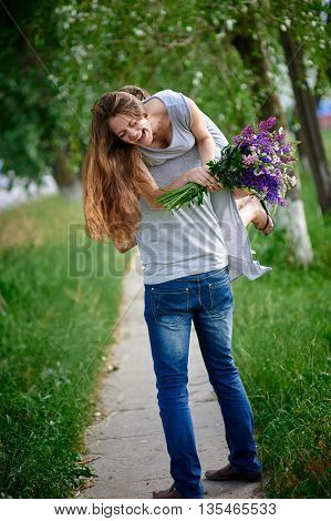 beautiful woman with a bouquet of lupine on the man's shoulder.