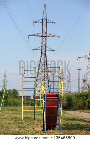 Children's Slide On Background Of The Power Lines