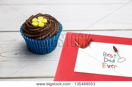 Word best dad ever on white background against delicious cupcake on a table