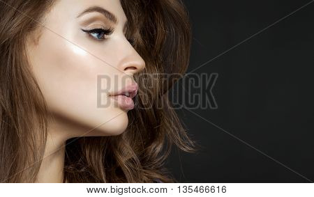 Close-up Portrait Of Beautiful Girl In Profile With Beautiful Hair And Make-up Professional On A Gra